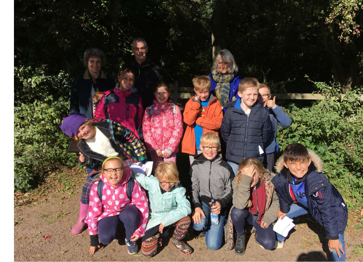 A group of children and adults pose for the camera in a woodland setting