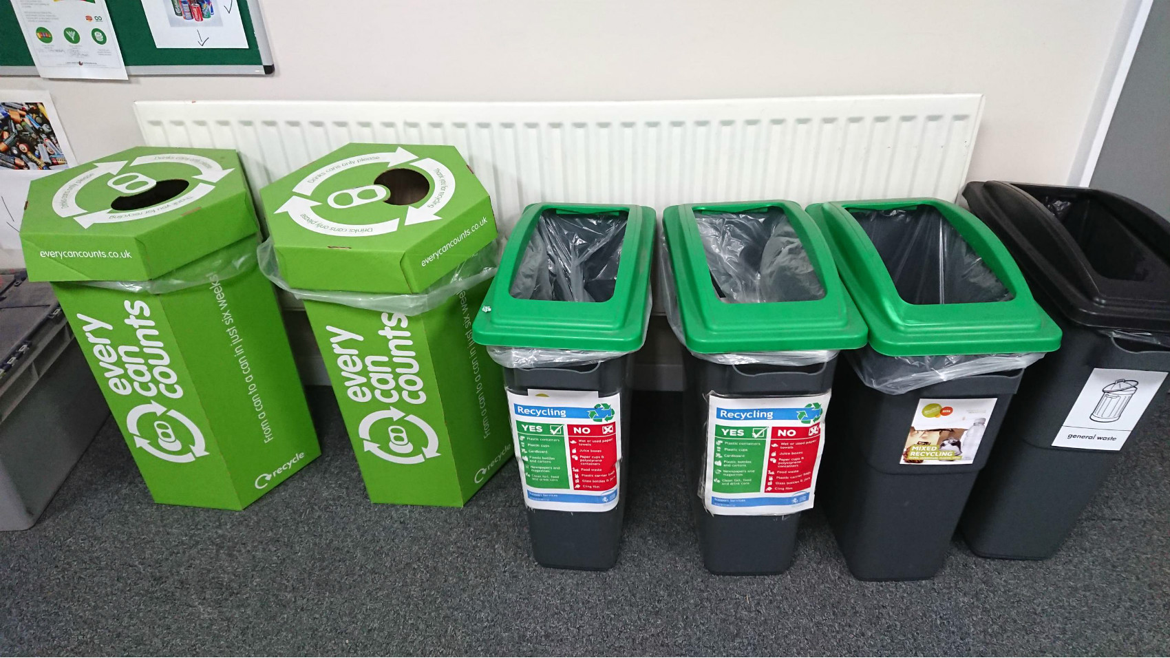 A row of different recycling containers, including some for cans and batteries, in an office at Canterbury Police Station.
