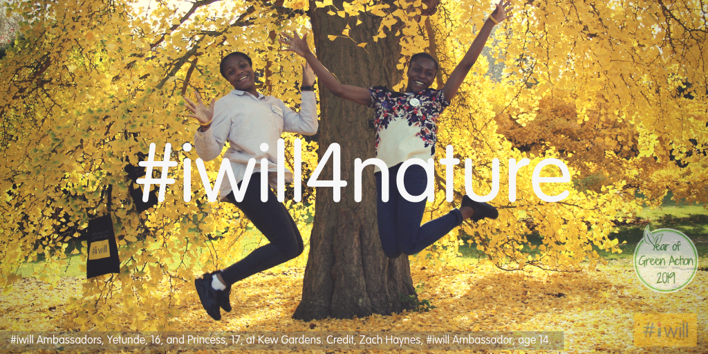 Two women jumping in the air in front of an autumn tree - the leaves are yellow. #iwill4nature