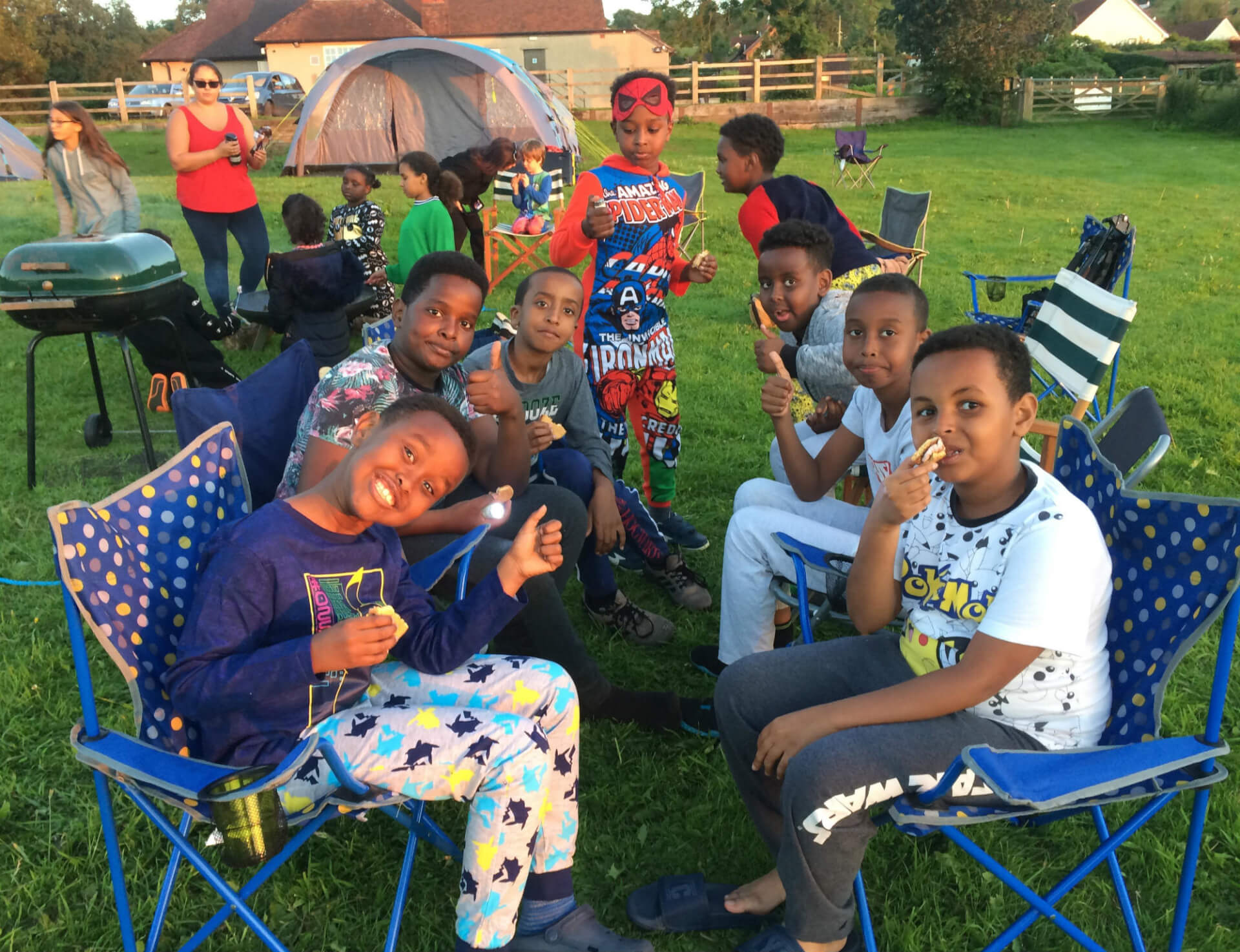 Children seated at the campsite eating dinner dressed in their pyjamas and giving a thumbs up.