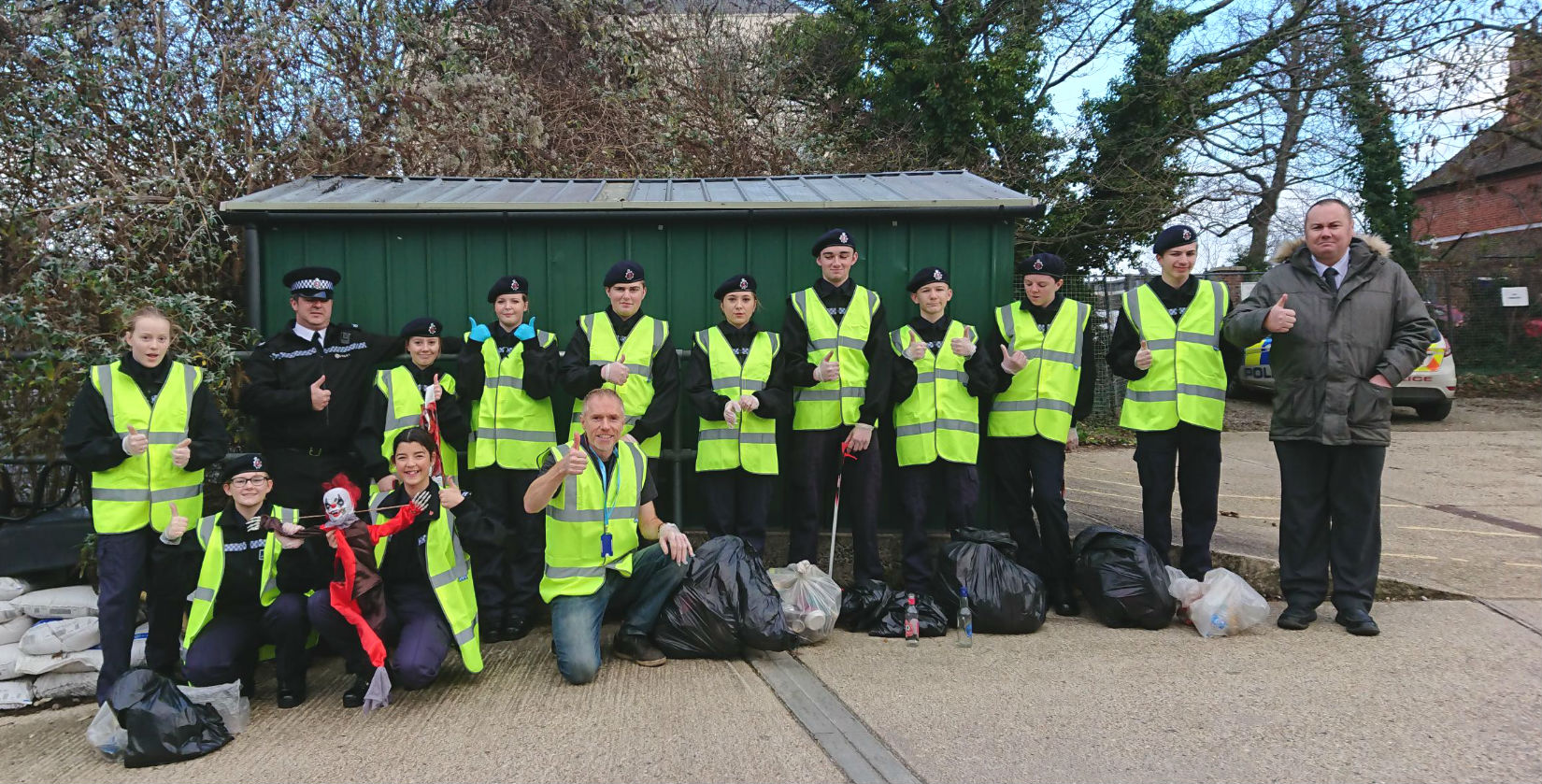 A photo of Canterbury and Dover Police Cadets lined up in high vis jackets giving the thumbs up with bags of collected litter at their feet