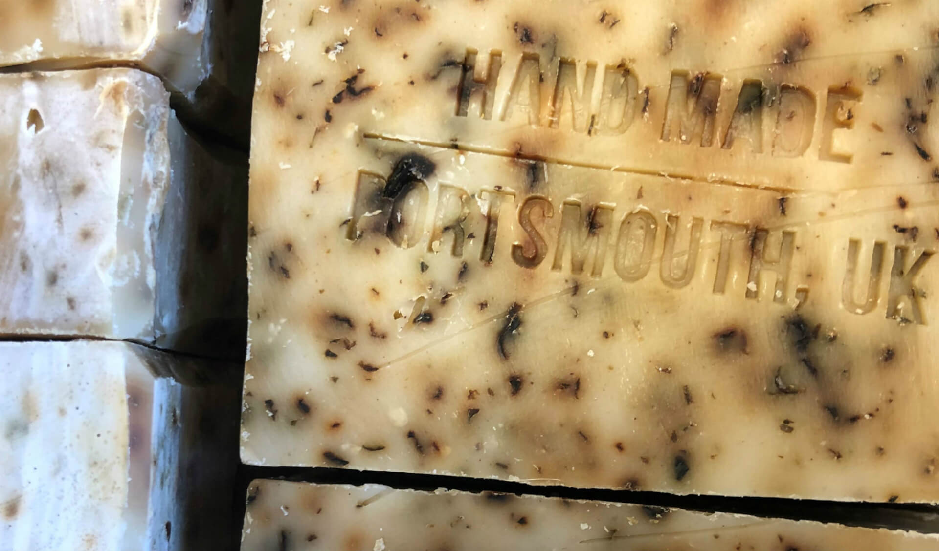 A close up of a number of soap bars embossed with the lettering 'Hand Made Portsmouth, UK'